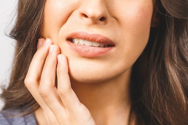 Mulher jovem com forte dor de dente, pressionando os dedos na bochecha