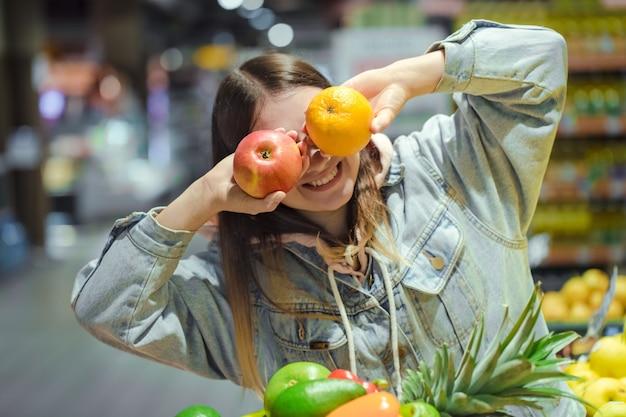 Mulher jovem com frutas nas mãos no supermercado.