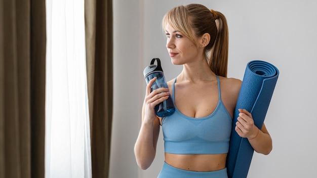 Mulher jovem com garrafa de água e tapete.