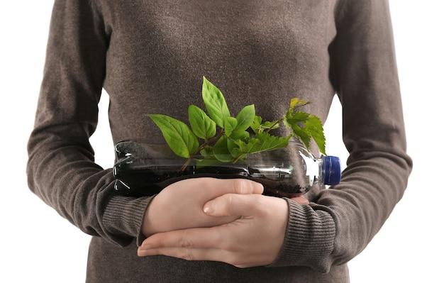 Mulher jovem com garrafa de plástico usada como recipiente para o cultivo de plantas contra a luz