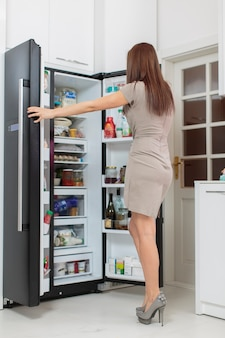Mulher jovem com geladeira