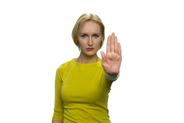 Mulher jovem com gola alta amarela fazendo gesto de pare com a palma da mão