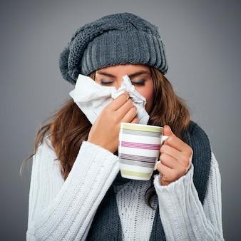Mulher jovem com gripe e assoando o nariz para um lenço