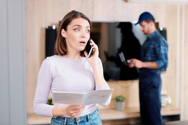 Mulher jovem com guia de instruções de uso, consultando serviço de conserto doméstico no telefone