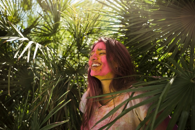 Mulher jovem, com, holi, cor, ligado, dela, rosto, ficar, perto, a, planta verde