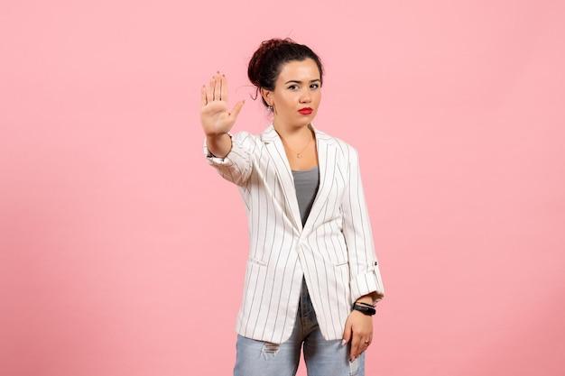 Mulher jovem com jaqueta branca mostrando o sinal de pare no fundo rosa.
