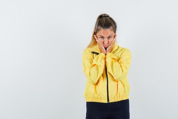Mulher jovem com jaqueta militar amarela e calça preta, colocando as mãos nas bochechas e parecendo uma fofa