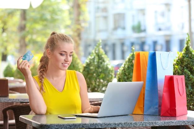 Mulher jovem com laptop e cartão de crédito em um café