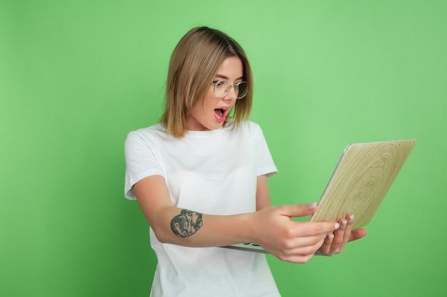 Mulher jovem com laptop isolado na parede verde do estúdio