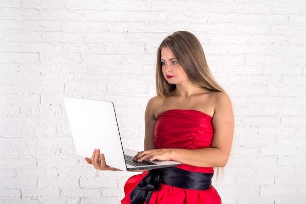 Mulher jovem com laptop na parede de tijolos