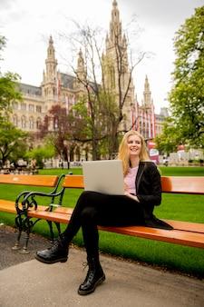 Mulher jovem com laptop no banco do parque em viena, áustria