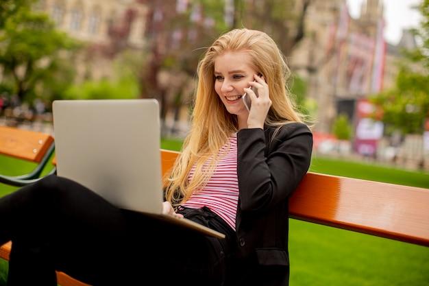 Mulher jovem com laptop no banco, usando o celular e sentada no parque em viena, áustria