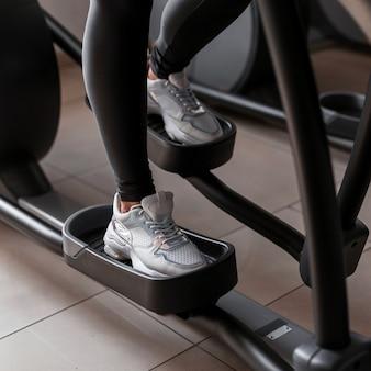Mulher jovem com leggings e tênis esportivos faz treinamento aeróbico em um simulador de stepper na academia
