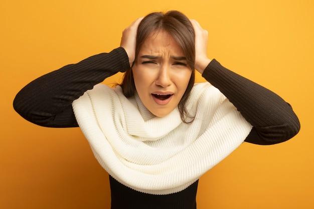 Mulher jovem com lenço branco de mãos dadas na cabeça gritando e gritando com expressão irritada