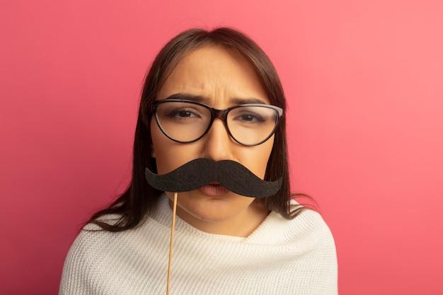 Mulher jovem com lenço branco de óculos segurando um bigode engraçado na vara com cara séria