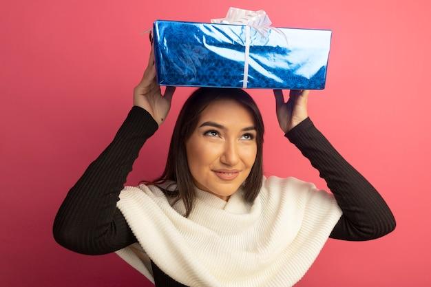 Mulher jovem com lenço branco segurando uma caixa de presente na cabeça e sorrindo com uma cara feliz em pé sobre a parede rosa