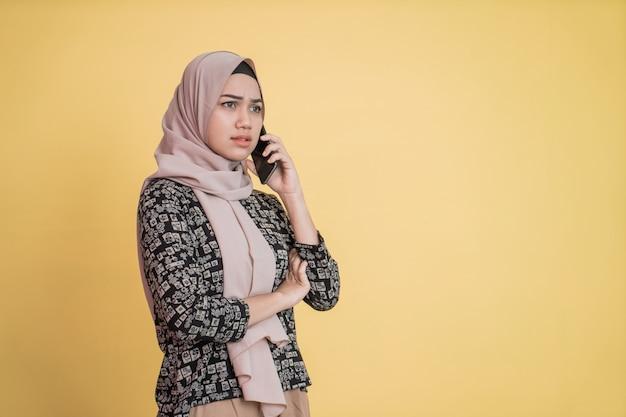 Mulher jovem com lenço na cabeça recebe uma ligação com um gesto de rosto admirado e com espaço