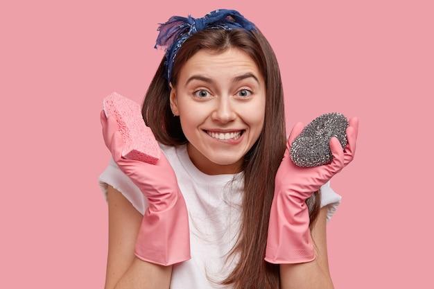 Mulher jovem com lenço na cabeça segurando produtos de limpeza