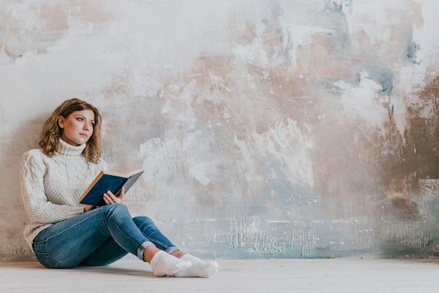 Mulher jovem, com, livro, perto, parede