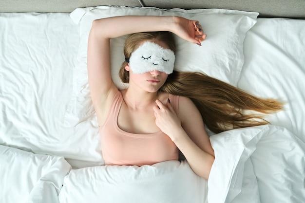 Mulher jovem com longos cabelos loiros e máscara de dormir nos olhos dormindo