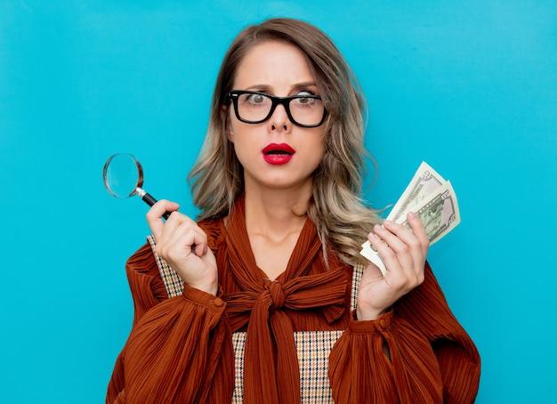 Mulher jovem com lupa e dinheiro no azul