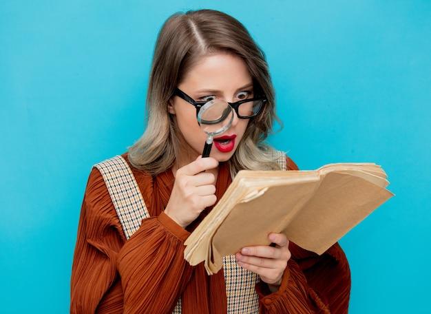 Mulher jovem com lupa e livros em azul