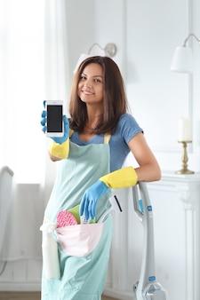 Mulher jovem com luvas de borracha mostrando smartphone