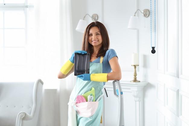 Mulher jovem com luvas de borracha mostrando tablet