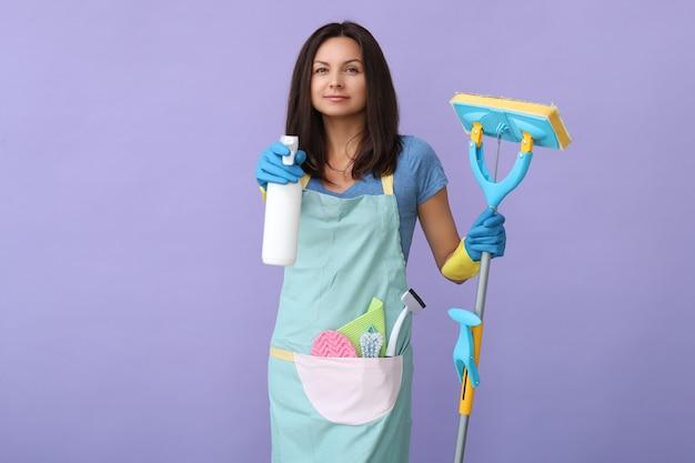Mulher jovem com luvas de borracha, pronta para limpar Foto gratuita