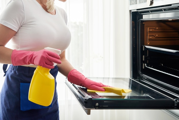 Mulher jovem com luvas de limpeza do forno na cozinha. conceito de serviço de limpeza