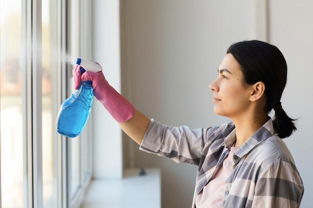 Mulher jovem com luvas limpando janela com spray de limpeza em casa