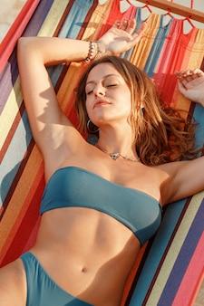 Mulher jovem com maiô azul deitada em uma rede ao pôr do sol