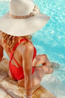 Mulher jovem com maiô vermelho e chapéu de palha relaxando perto de uma piscina com as pernas na água