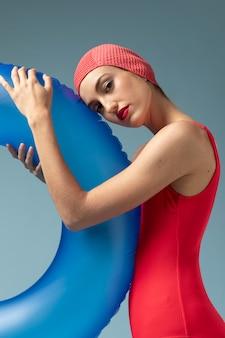 Mulher jovem com maiô vermelho e uma argola de natação