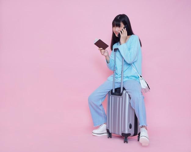 Mulher jovem com mala e falando no telefone na parede rosa