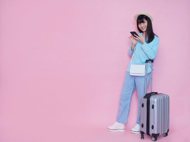 Mulher jovem com mala e smartphone na parede rosa