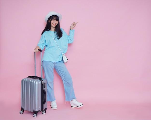 Mulher jovem com mala na parede rosa