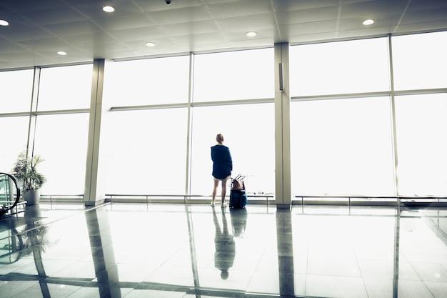Mulher jovem com mala olhando para grandes janelas no terminal do aeroporto