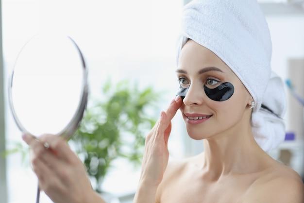 Mulher jovem com manchas pretas embaixo dos olhos e com uma toalha na cabeça, olhando no espelho da casa