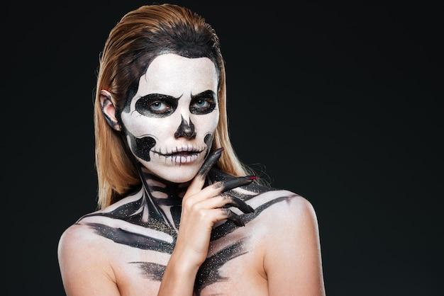 Mulher jovem com maquiagem de esqueleto gótico sobre fundo preto