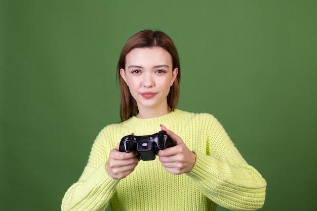 Mulher jovem com maquiagem natural perfeita, lábios grandes castanhos em suéter casual na parede verde com joystick jogando videogame