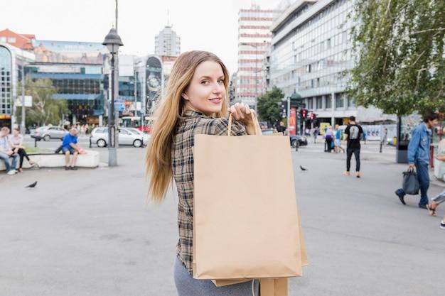 Mulher jovem, com, marrom, bolsas para compras, ficar, ligado, pavimento