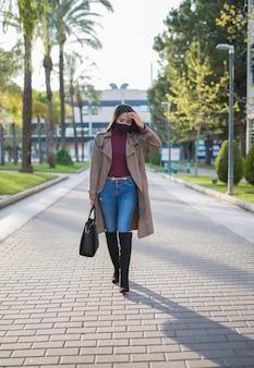 Mulher jovem com máscara andando preocupada na rua. focado em seus pensamentos