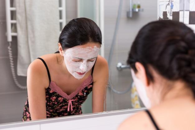 Mulher jovem com máscara cosmética lavando o rosto em frente ao espelho no banheiro moderno de azulejos de casa