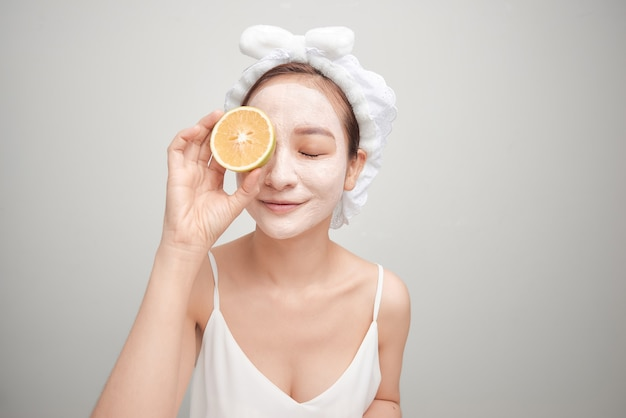 Mulher jovem com máscara de argila facial segurando uma fatia de fruta laranja cobrindo os olhos