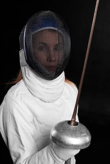 Mulher jovem com máscara de esgrima e traje branco com espada e olhar para a frente