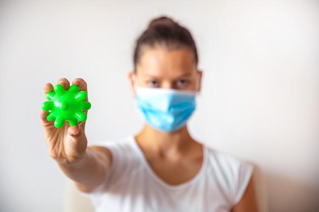 Mulher jovem com máscara de medicamento com bola de plástico verde como vírus na mão no fundo branco, conceito médico, pare o coronavírus covid-19 conceito