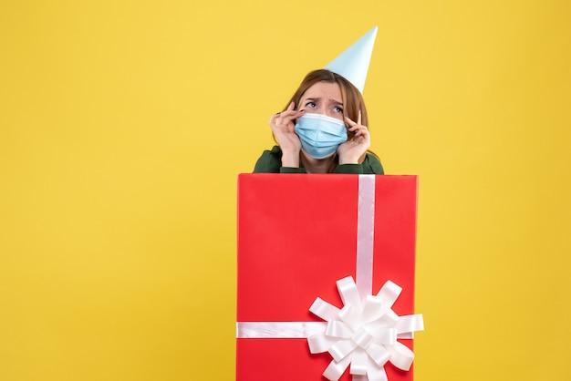 Mulher jovem com máscara dentro da caixa de presente e rosto triste