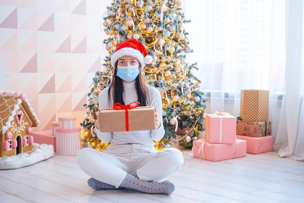 Mulher jovem com máscara e presentes no natal