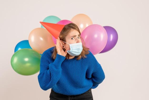 Mulher jovem com máscara estéril e vista frontal, escondendo balões coloridos nas costas